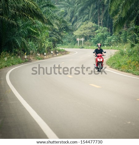 Man in helmet riding a motorbike on a roadway - stock photo