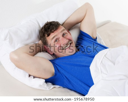 man in his fifties lying in bed and smiling