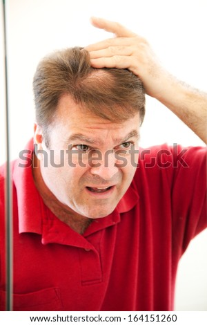 Man in his forties looking in the mirror discovers a bald spot in his hair.   - stock photo