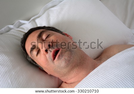 Man in his forties (40s) snoring in bed. Health care concept . copy space  - stock photo