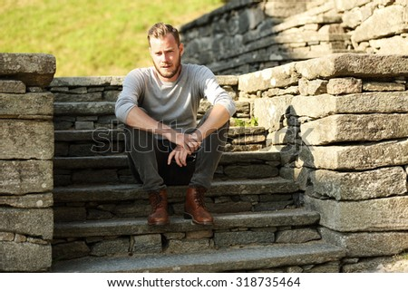 Man in his 20s wearing a grey shirt and jeans, sitting down outside on a set of steps on a sunny summer day.  - stock photo