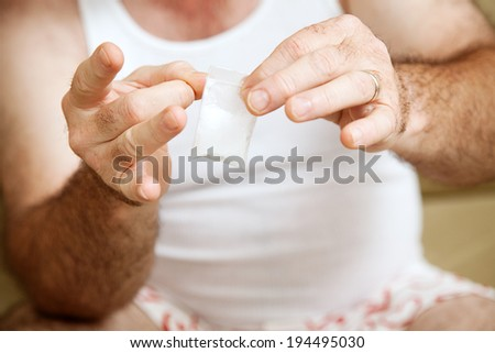 Man in his underwear holding a gram bag of cocaine.   - stock photo