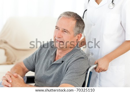 Man in his wheelchair with his nurse at home