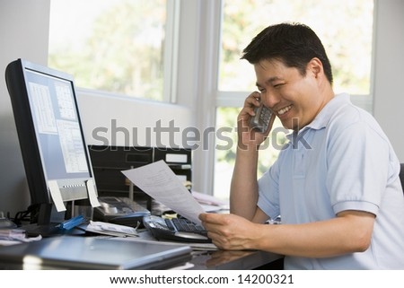 Man in home office with computer and paperwork on telephone smiling
