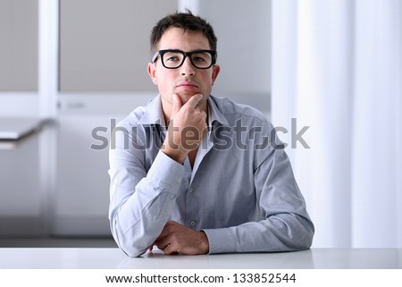 Man in home office with thoughtful look - stock photo