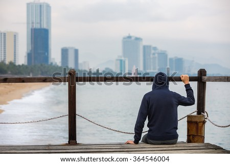 Man in hood sitting on wooden pier, shot from behind. Emigration concept