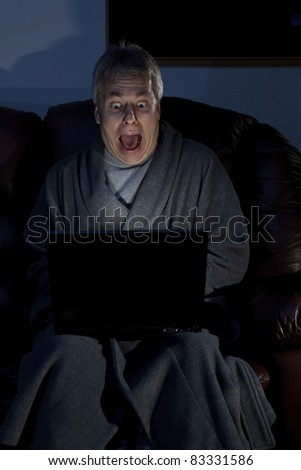 Man in housecoat working late series shocked computer crash - stock photo