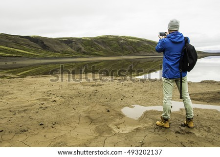 Man in Iceland on the edge of the lake photographs beautiful landscape on the phone