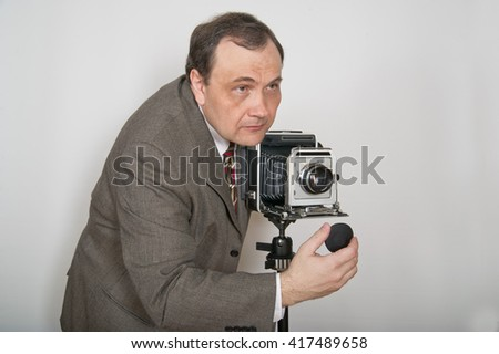 Man in jacket and tie aiming retro photo camera