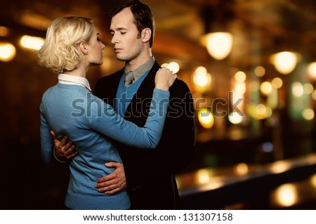 Man in jacket embracing woman in blue cardigan outdoors at night
