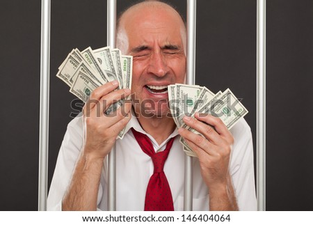 Man in jail crying and holding cash - stock photo