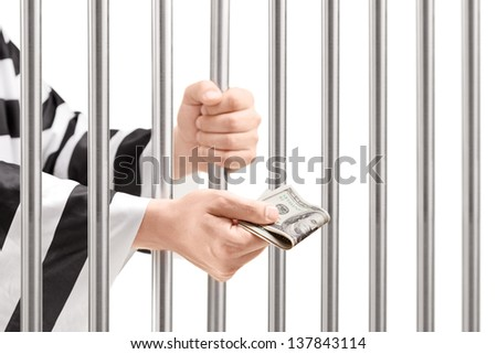 Man in jail holding prison bars and giving bribe isolated on white background - stock photo