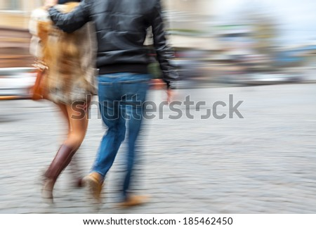 Man in jeans and a woman in a fur coat walking down the street hugging. Intentional motion blur