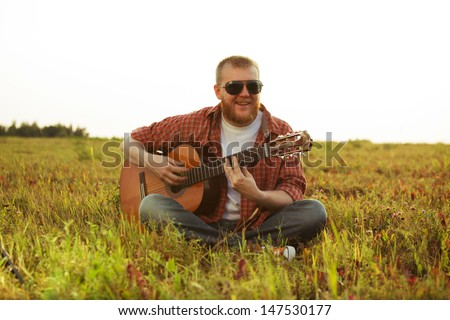 Man in jeans sits on grass and plays guitar