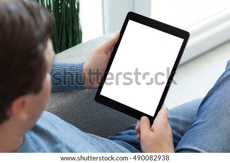 man in jeans sitting on sofa and holding tablet computer with isolated screen