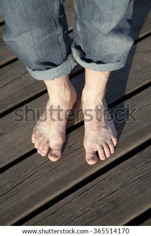 Man in jeans standing on a wooden pier with bare feet