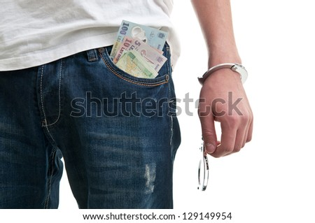 Man in jeans with handcuffs and money in pocket - stock photo