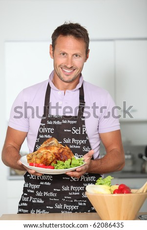 Man in kitchen with apron cooking chicken - stock photo