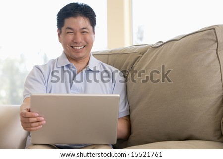 Man in living room using laptop and smiling - stock photo