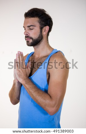 Man in lotus pose with eyes closed in fitness studio