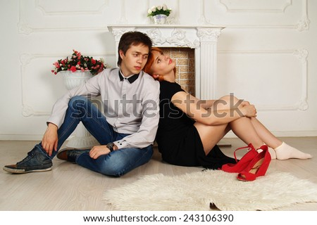 Man in love and the woman sit on a floor before a fireplace