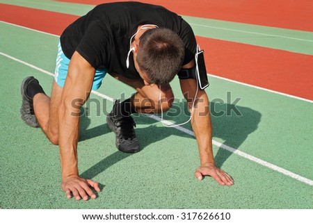 Man in low start position on stadium. Athlete in starting position. Male runner  listening to music on mp3 player or mobile phone. Running, jogging, cardio, sport, active lifestyle concept