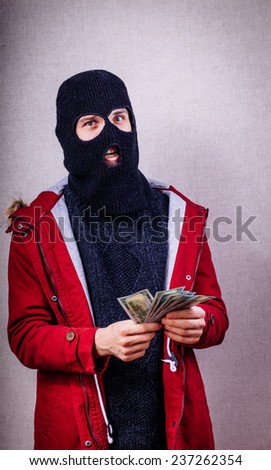 man in mask holding dollars - stock photo
