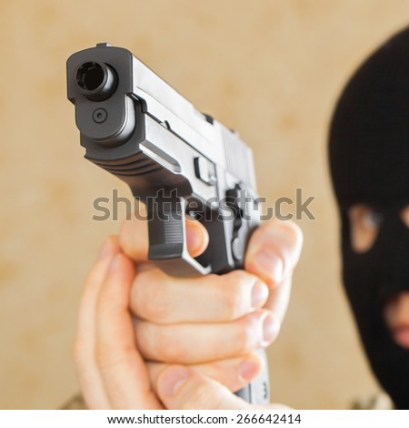 Man in mask holding gun and ready to use it - studio shot - stock photo