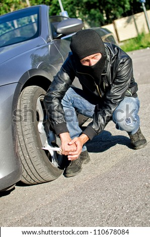 Man in mask punctures a car tyre. Revenge concept - stock photo