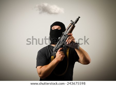 Man in mask with gun and white cloud. Imagination concept.