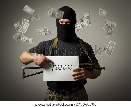Man in mask with gun is holding white paper with a sign. Ransom, tribute and racketeering concept. One million dollars.