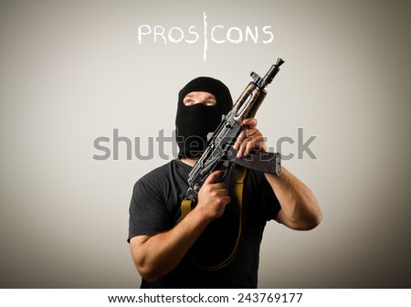 Man in mask with gun. Pros and cons concept.