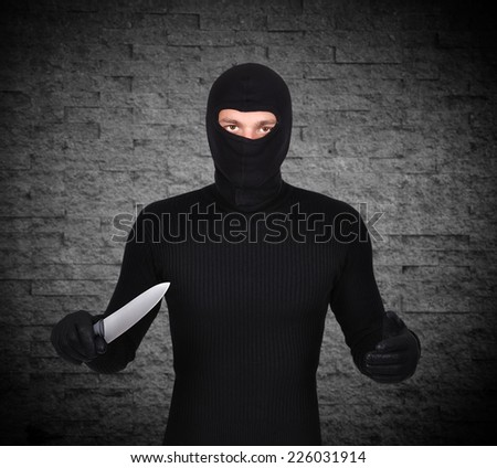 man in mask with knife on gray  background - stock photo