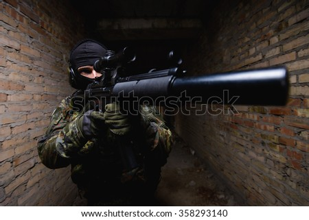 Man in military uniform and black mask with gun in his hand standing in dark corridor/Man in black mask with gun