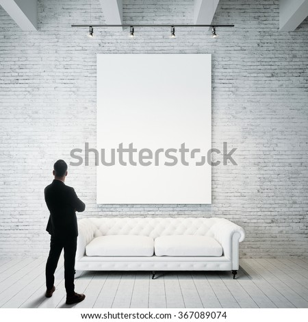 Man in modern suit looking at empty canvas holding on the brick wall and vintage classic sofa.  - stock photo