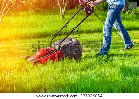 Man in motion with lawnmower and mows green grass - stock photo