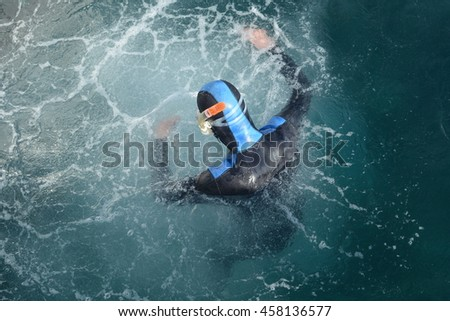 Man in neoprene suit is surrounded by deep blue water,  his head is above the sea surface