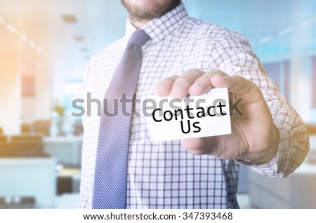 Man in office holding a card with a message written on it: Contact Us - stock photo