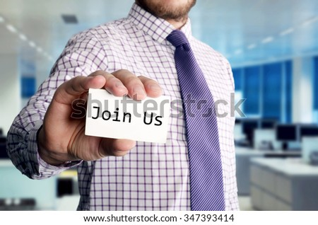 Man in office holding a card with a message written on it: Join Us - stock photo