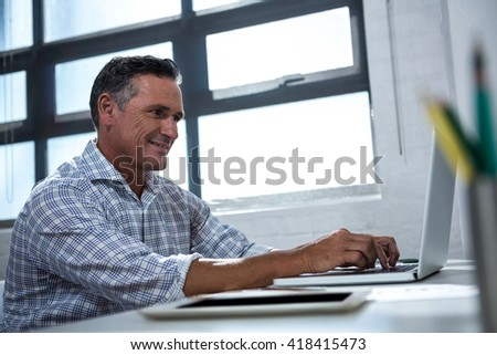 Man in office sitting at desk using laptop