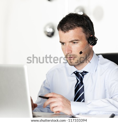 man in office with laptop and headset on his head - stock photo