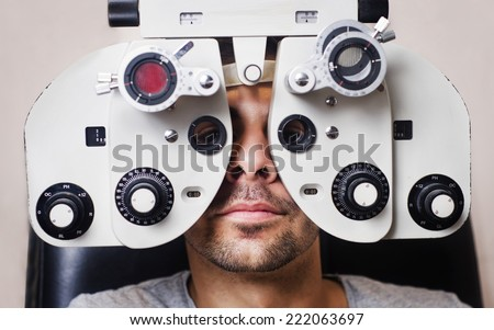 Man in optometrist phoropter ready for eye calibration, health care image.