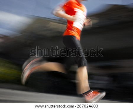 Man in orange and black dress in blurred motion running in competition in city - stock photo
