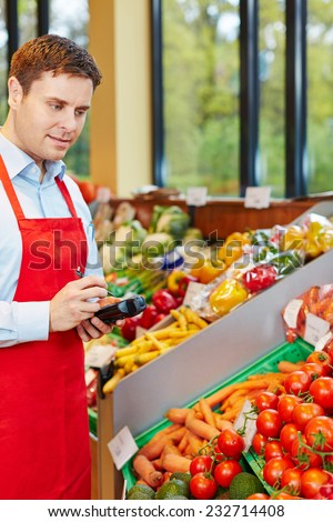Man in organic food store ordering vegetables with mobile data acquisition terminal