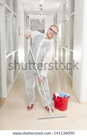 Man in Overall Cleaning Office Corridor with Laugh