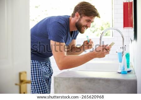 Man In Pajamas Brushing Teeth And Using Mobile Phone - stock photo