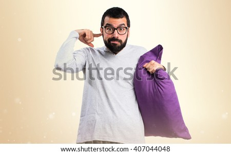 Man in pajamas covering his ears - stock photo