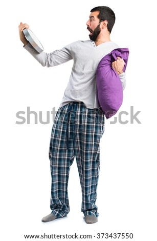 Man in pajamas holding clock