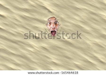Man in panic - sunken in the sand - stock photo