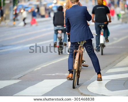 Man in perfect sui with phonet and old bike, typical Stockholm Scene - stock photo